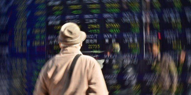 A pedestrian looks at a screen showing movements for the Tokyo Stock Exchange in Tokyo on January 14,...