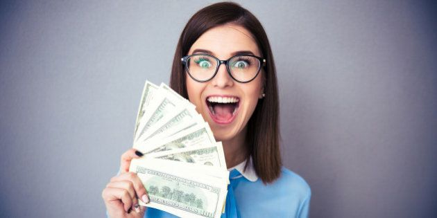 Laughing businesswoman holding bills of dollar and shouting over gray background. Wearing in blue shirt...