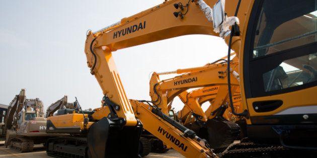 Hyundai Heavy Industries Co. excavators stand parked at the Hyundai Heavy Industries Co. plant in Ulsan,...