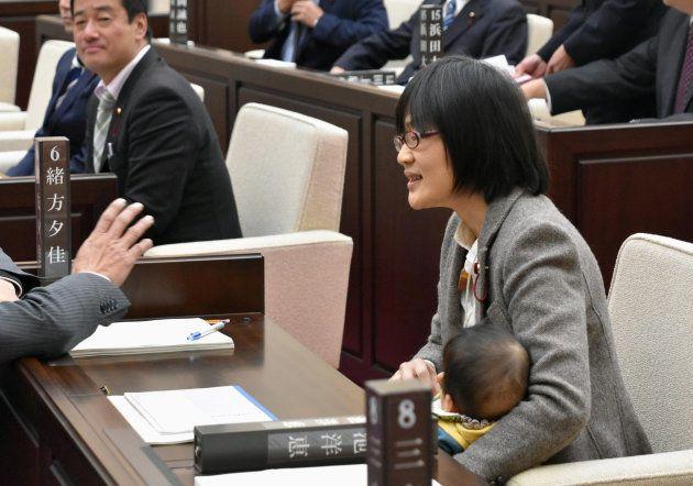 当時生後7カ月の長男を抱いて議場に座る緒方さん