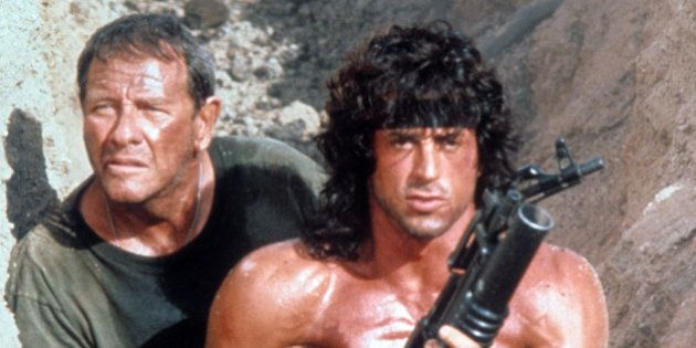 Sylvester Stallone walks through a trench with Richard Crenna in a scene from the film 'Rambo III', 1988....