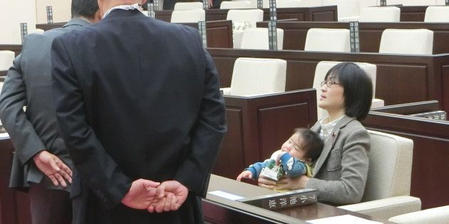 熊本市議会に生後7カ月の長男を抱いたまま出席し、議会事務局職員らによる退席要請を拒否する緒方夕佳議員(右)=2017年11月22日、熊本市中央区