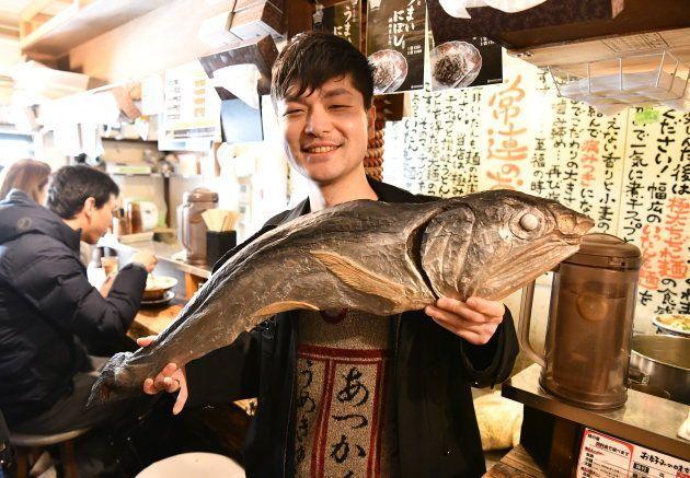煮干しの巨大彫刻を持つ大曽根悠二郎さん=東京・新宿
