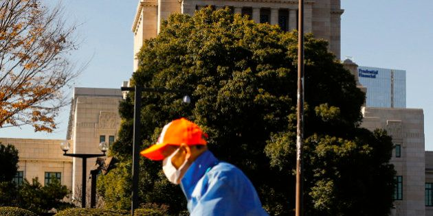 A worker blows leaves off the pavement outside the Diet building, the seat of Japan's parliament, in...