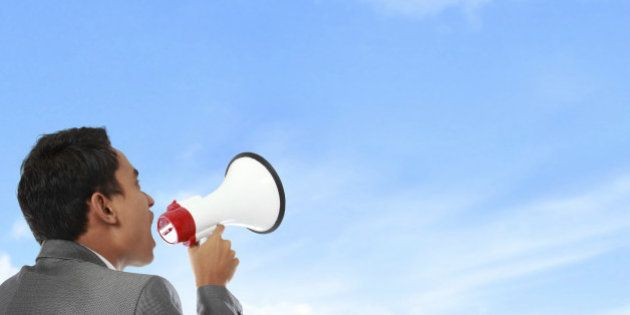business man shouting using megaphone under the blue