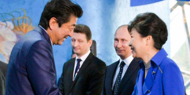 South Korean President Park Geun-hye, right, and Japanese Prime Minister Shinzo Abe, left, shake hands...