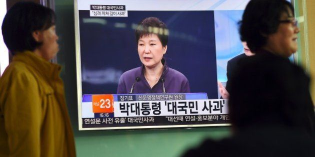 People walk past a television screen showing South Korean President Park Geun-Hye making a public apology,...