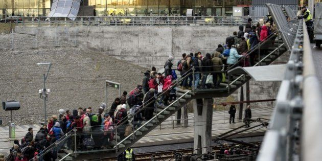 Police organize the line of refugees on the stairway leading up from the trains arriving from Denmark...