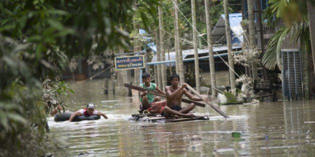 Flood-affected residents use make-shift rafts to travel through floodwaters in Kalay, upper Myanmar's...