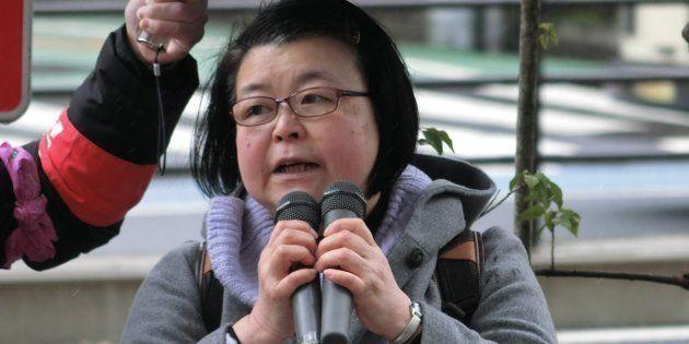 2月22日、みぞれの降るなか、昨年末まで働いていた職場の前で、雇止めは不当だと訴える渡辺照子さん