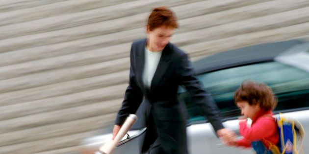 Businesswoman and child holding hands, blurred
