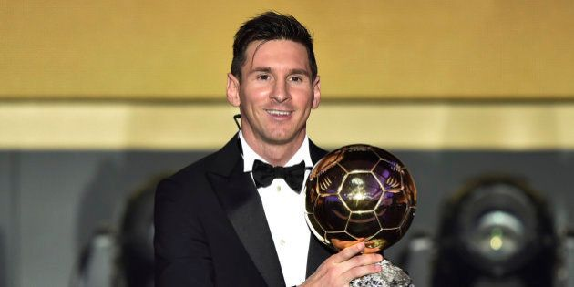 TOPSHOT - FC Barcelona and Argentina's forward Lionel Messi poses with trophy after receiving the 2015...