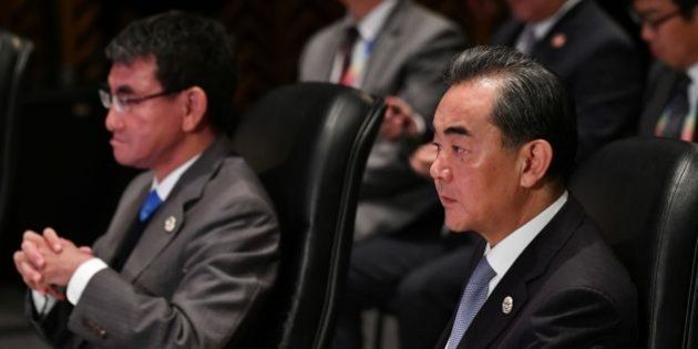 China's Foreign Minister Wang Yi (R) and Japan's Foreign Minister Taro Kono (L) listen to the opening...