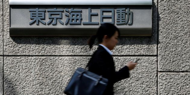 A woman walks past a sign of Tokio Marine & Nichido Fire Insurance Co at the company's headquarters in...