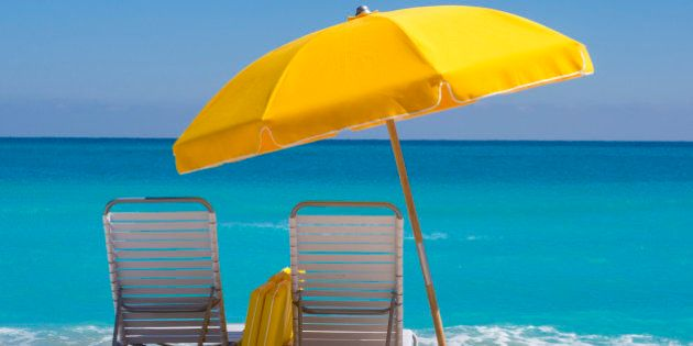 'Yellow Beach umbrella and deck chairs on the beach on a clear day on South beach,