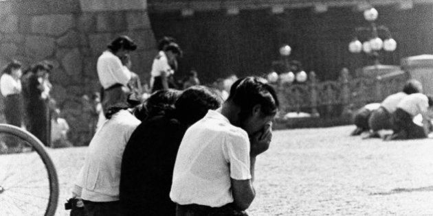 Schoolgirls weep in sorrow and shame in the Imperial Plaza before Emperor Hirohito's palace in Tokyo...