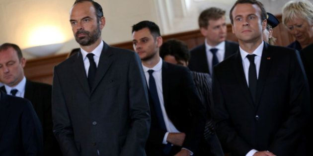 French Prime Minister Edouard Philippe (L) and French President Emmanuel Macron attend a mass to pay...