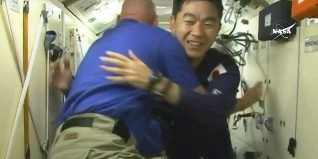 In this image taken from video from NASA, Japanese astronaut Kimiya Yui, right, is greeted as he boards...