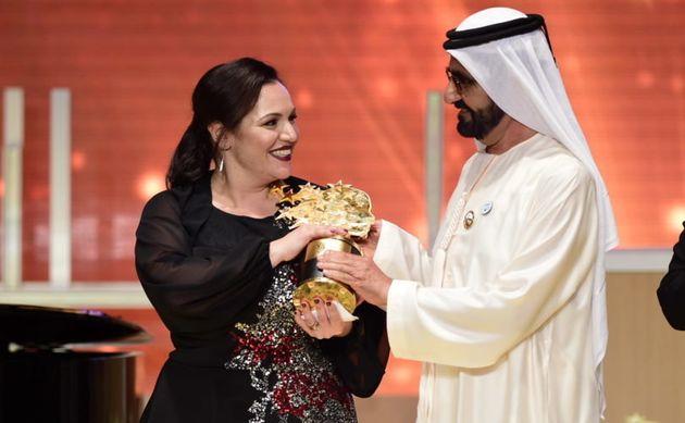 優勝してトロフィーをもらうアンドリア・ザフィラクさん=Global Teacher