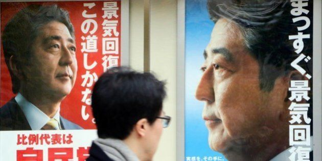 A man walks past posters of Japanese Prime Minister and ruling Liberal Democratic Party (LDP) leader...