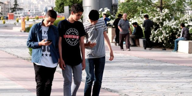 Iranian youth use their mobile phones as they walk at a park in Tehran, Iran, May 16, 2017. REUTERS/TIMA...