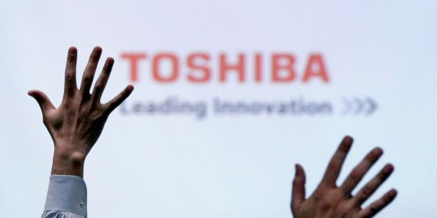 Reporters raise their hands for a question during a news conference by Toshiba Corp CEO Satoshi Tsunakawa...