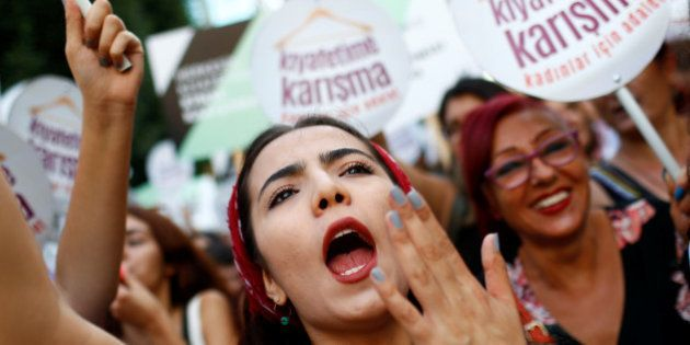 Women rights activists shout slogans during a protest against what they say are violence and animosity...