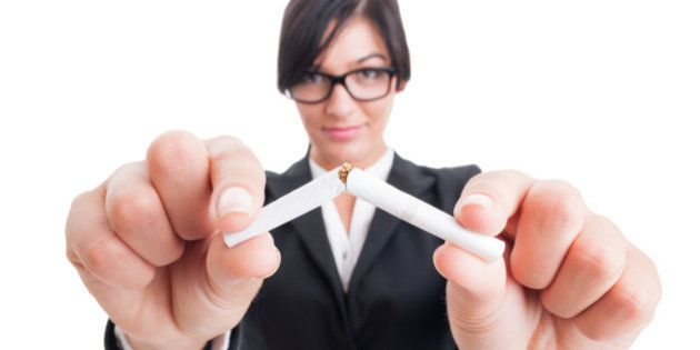 Business woman breaking a cigarette in half. Stop or quit smoking