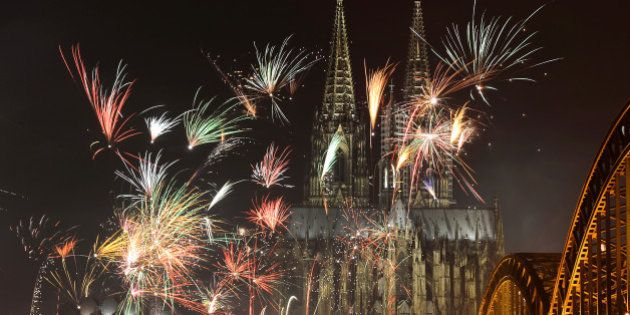 Fireworks light up the Dom church on the Rhine river in Cologne, western Germany after midnight on January...