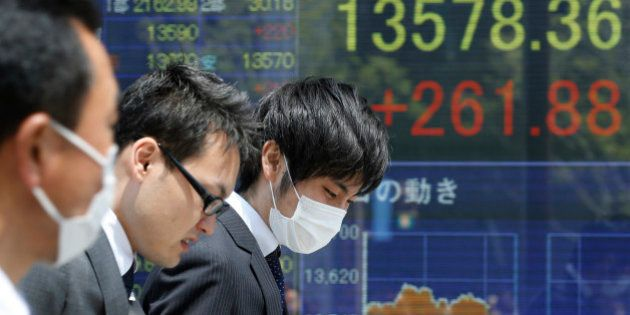 People walk by an electronic stock board of a securities firm showing Japan's benchmark Nikkei stock...