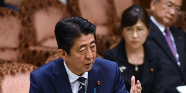 Japan's Prime Minister Shinzo Abe (L) answers questions during a budget dommittee meeting in the Upper...