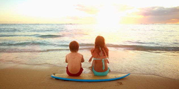 Caucasian children sitting on surfboard on tropical