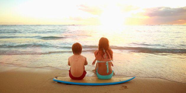 Caucasian children sitting on surfboard on tropical