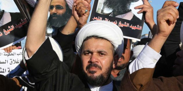 Iraqi Shiite protesters chant slogans against the Saudi government as they hold posters showing Sheikh...