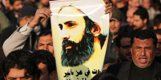 An Iraqi man holds a portrait of prominent Shiite Muslim cleric Nimr al-Nimr during a demonstration against...