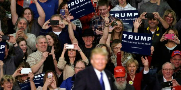Supporters reacts as Republican presidential candidate Donald Trump speaks during a campaign rally at...