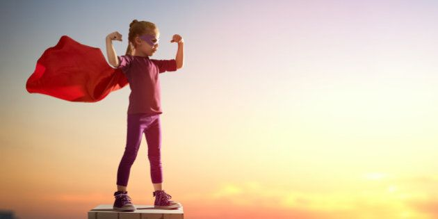 Little child girl plays superhero. Child on the background of sunset sky. Girl power