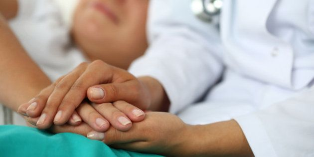 Friendly female doctor's hands holding patient's hand lying in bed for encouragement, empathy, cheering...