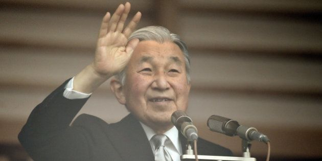 Japanese Emperor Akihito waves to well-wishers from the balcony of the Imperial Palace in Tokyo on December...