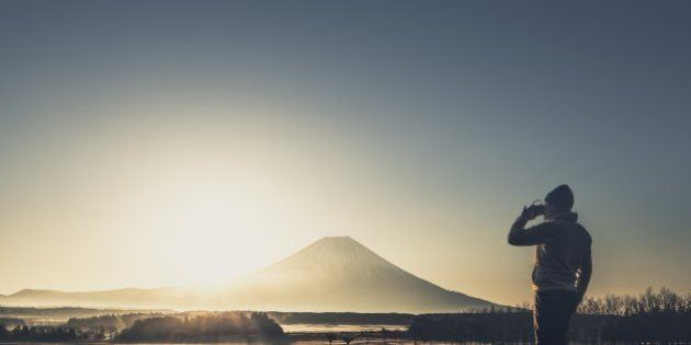 View of man drinking coffee in front of Mt. Fuji at