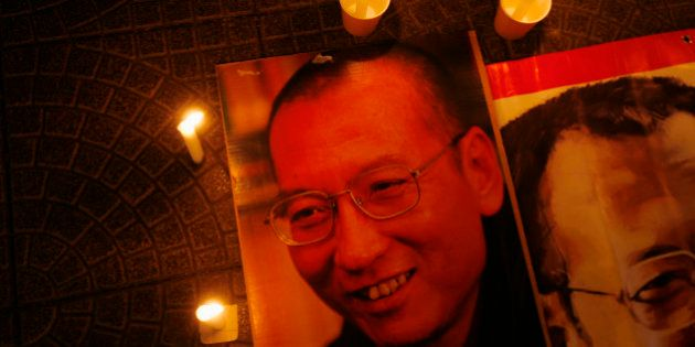 Candles are placed around portraits of jailed Chinese pro-democracy activist Liu Xiaobo during a candlelight...