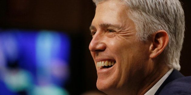 U.S. Supreme Court nominee judge Neil Gorsuch smiles in reaction to a question as he testifies during...