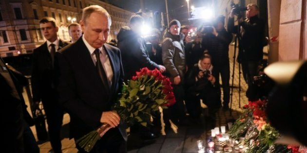 Russian President Vladimir Putin, left, lays flowers at a place near the Tekhnologichesky Institut subway...