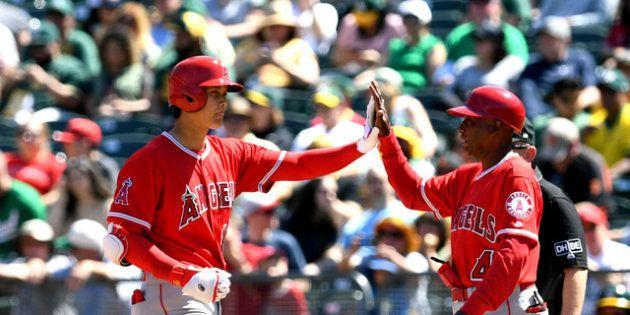 エンゼルス戦で右前安打を放ち、一塁コーチとハイタッチする大谷=白井伸洋撮影
