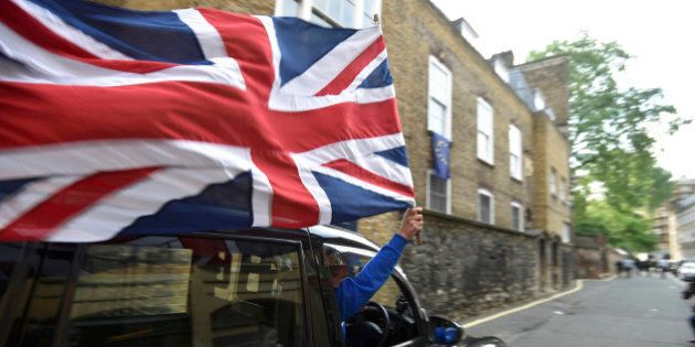 A taxi driver holds a Union flag, as he celebrates following the result of the EU referendum, in central...
