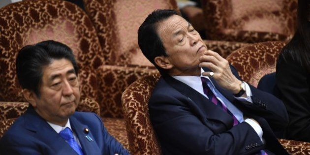 Japanese Prime Minister Shinzo Abe (L) and Finance Minister Taro Aso (R) attend a budget committee session...