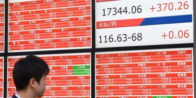 A pedestrian looks at a stock market share prices board in Tokyo on November 18, 2014. Tokyo stocks rose...