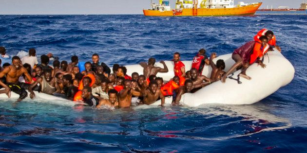 In this photo taken on Sunday, April 17, 2016 migrants ask for help from a dinghy boat as they are approached...