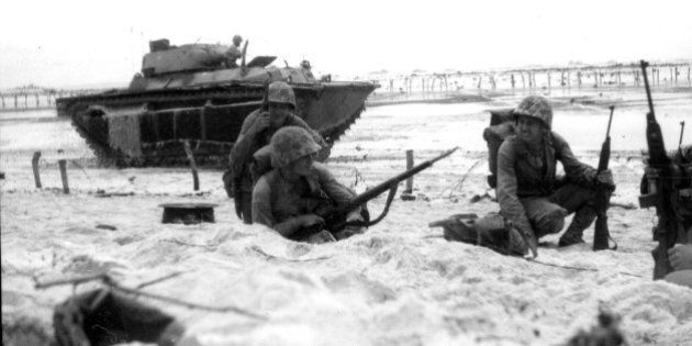 Marines moving along the beach cautiously while an amphibious tank covers them, Peleliu, Palau, September...