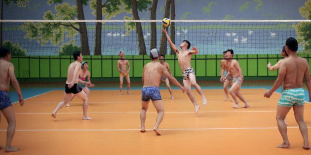 North Koreans dressed in their swim suits play a round of volleyball at the Munsu water park on Tuesday,...